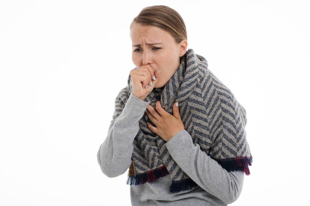 אישה בסוודר משתעלת